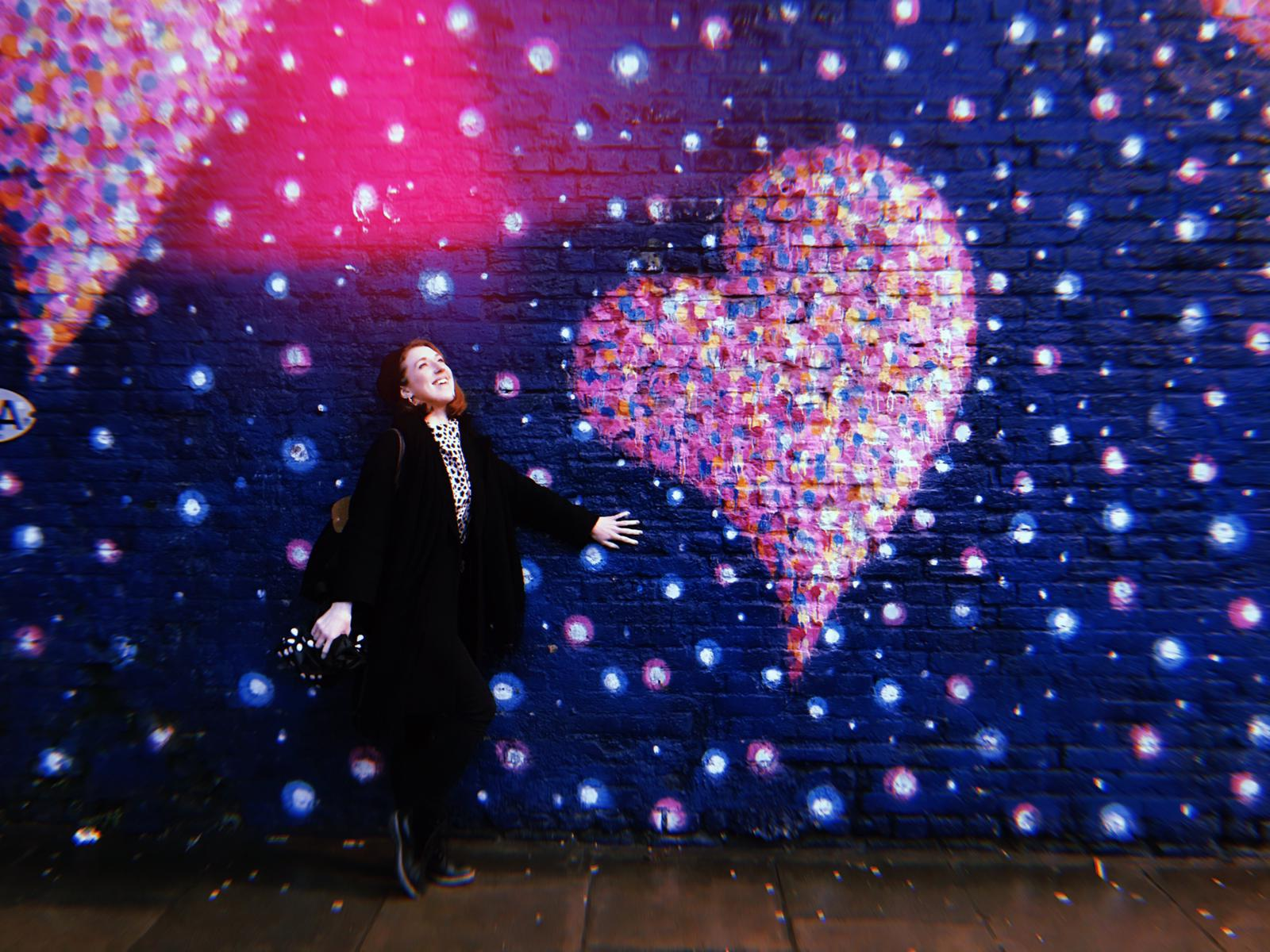 A Photo of Lydia standing next to a wall painting of a love heart