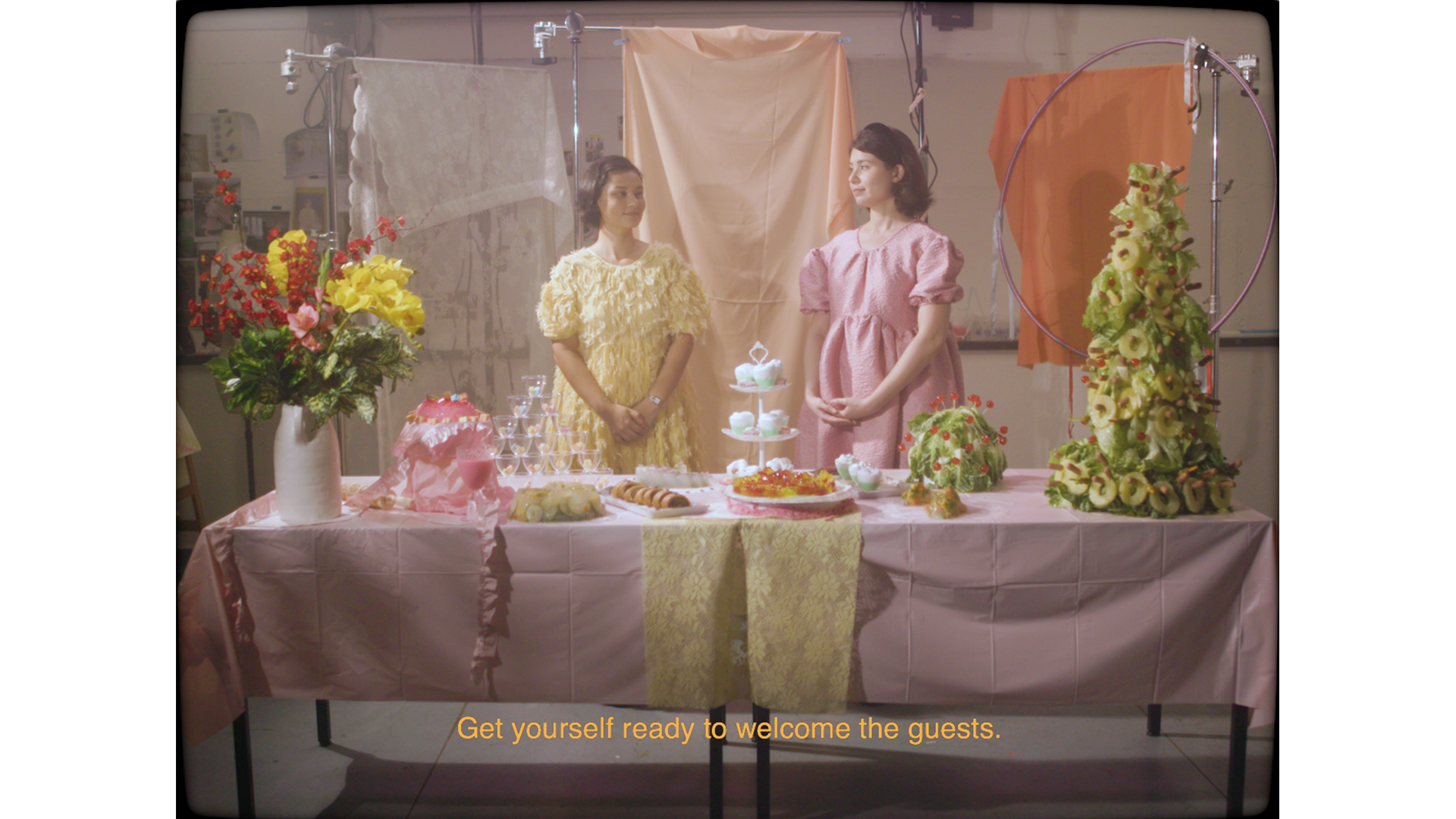 film still of 2 formally dressed women behind a table decorated with flowers