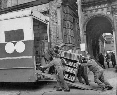 Black and white photograph of removal men putting a trolley of books into a van