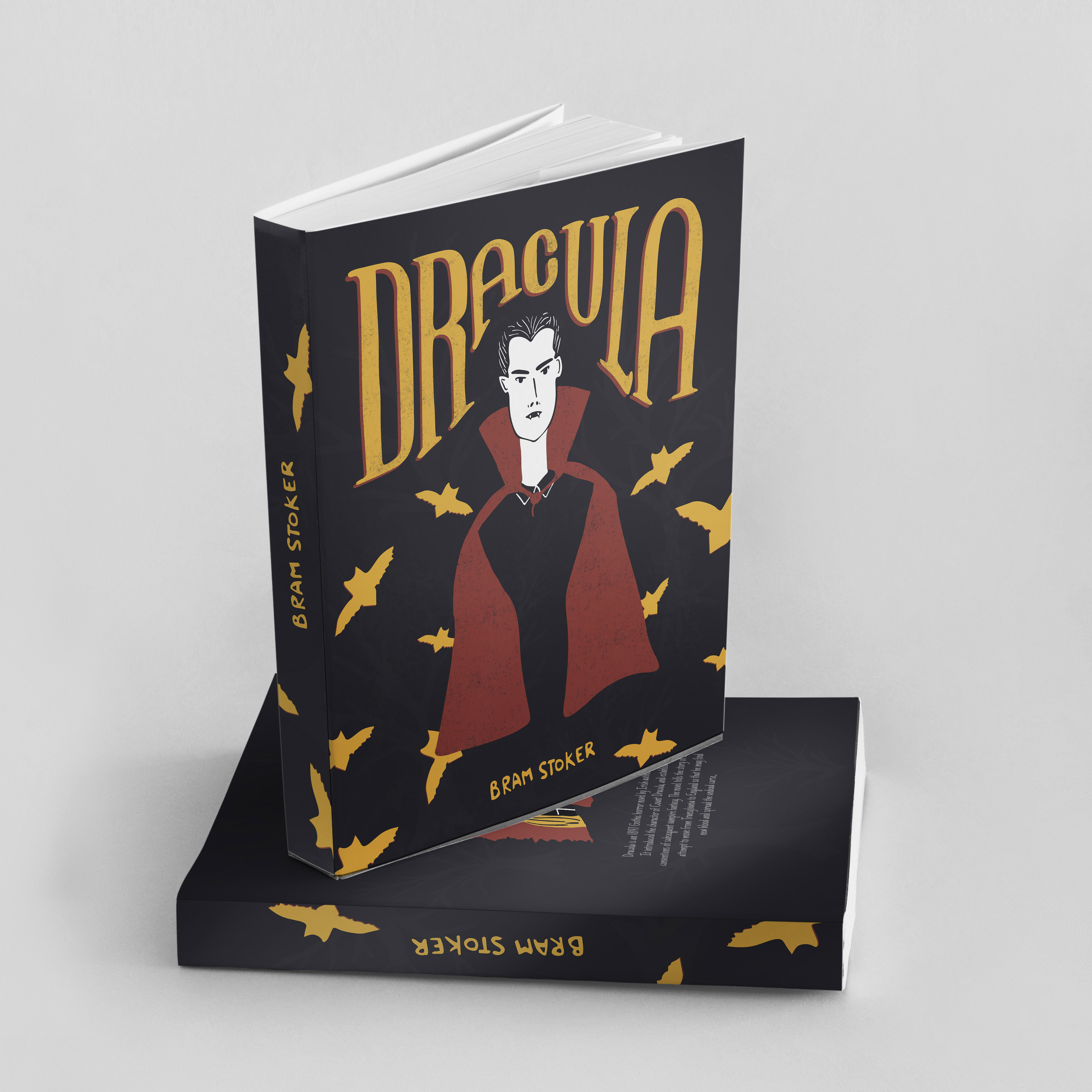 A photo of an illustrated book cover about Dracula. The cover is all black with orange font and Dracula in a red cape with orange bats flying around. The book is propped up under another book.