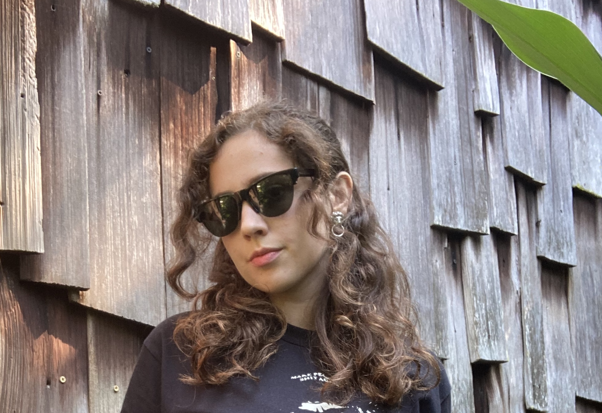 A photo of Ingrid Jensen wearing sunglasses, a black t shirt and a pair of denim jeans
