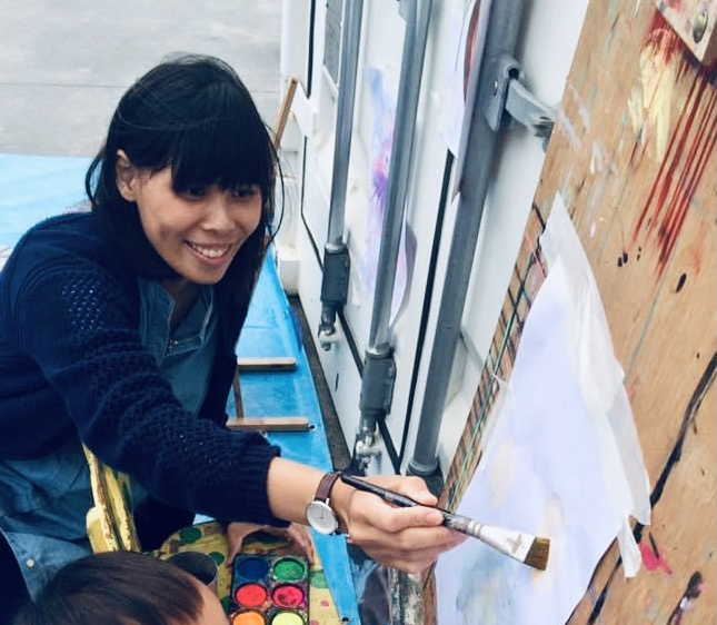A Photo of How Yan Betty painting on a canvas