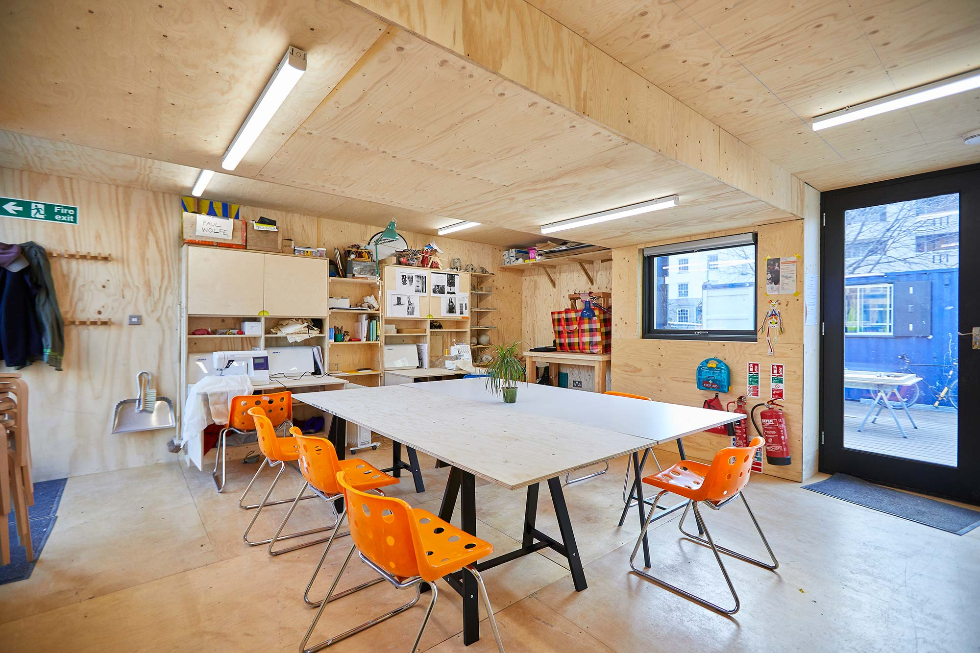 Studio space with making tools, a table and orange chairs