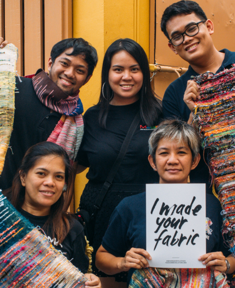"""5 garment workers posing, with one holding a sign in the bottom right that reads """"I made your fabric"""""""