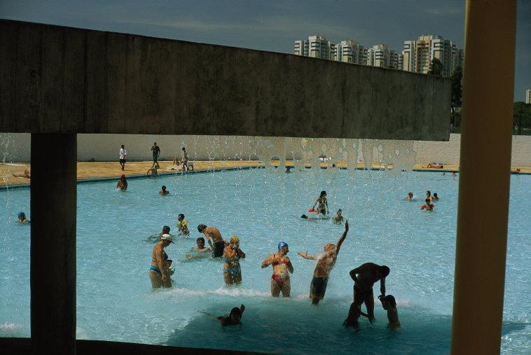 """BRAZIL. Sao Paulo. The largest pool in Sao Paulo draws working class Paulistanos - but not the cities affluent population. """"You would never see a rich person here"""" says a city resident. Terrified of crime, the wealthy live in walled, gated enclaves protected by armed guards. 2002."""
