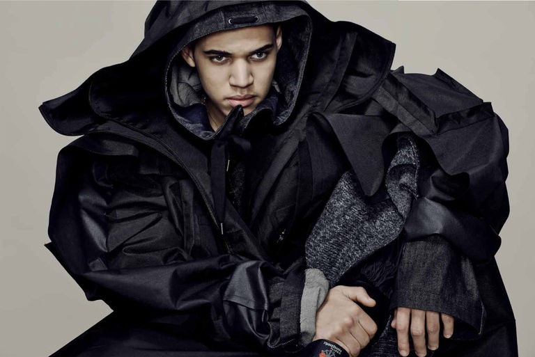 Male Model In Hooded Coat Crouching On The Ground