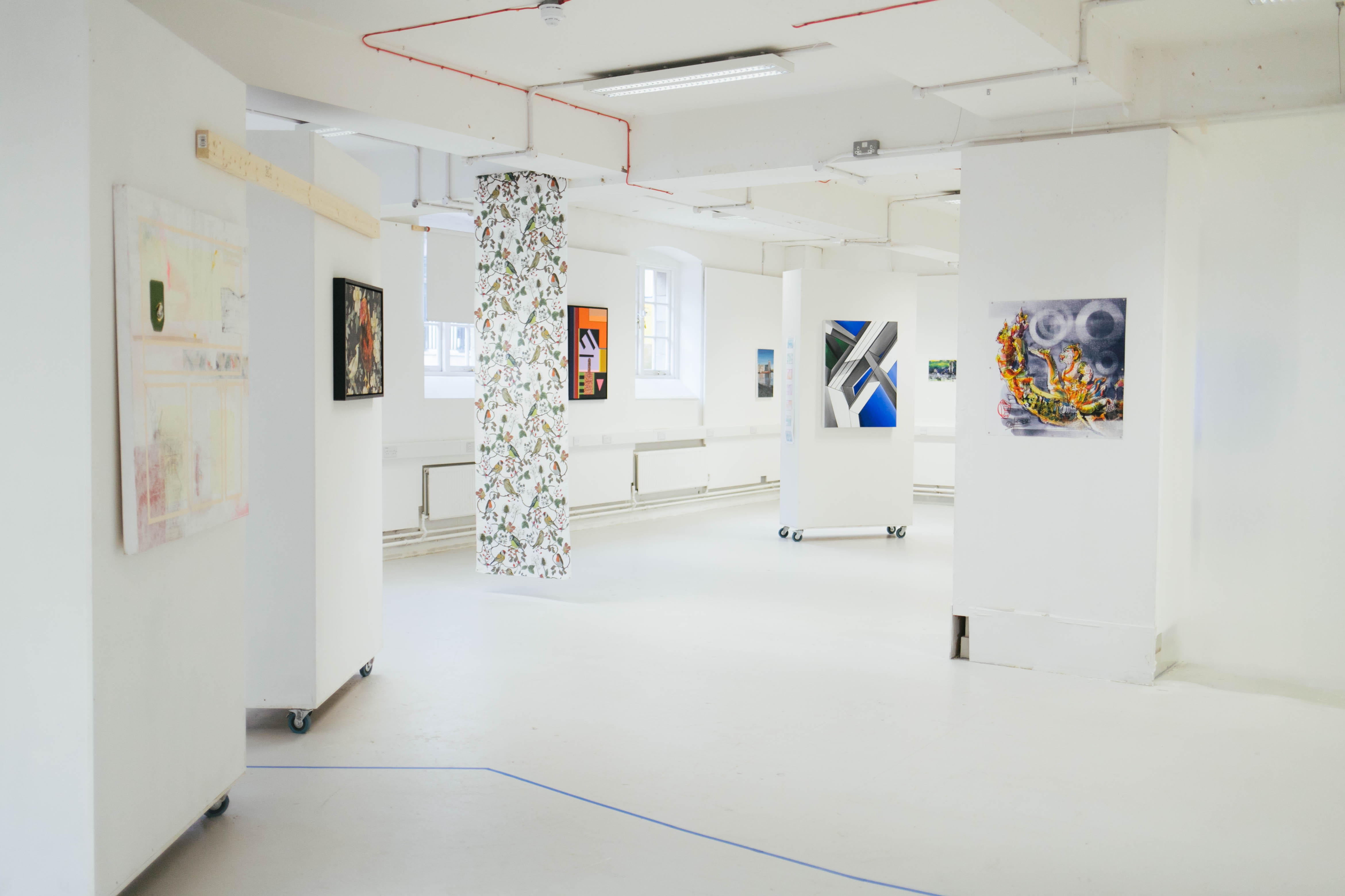 A photo of an empty art exhibit with art pieces mounted across the room