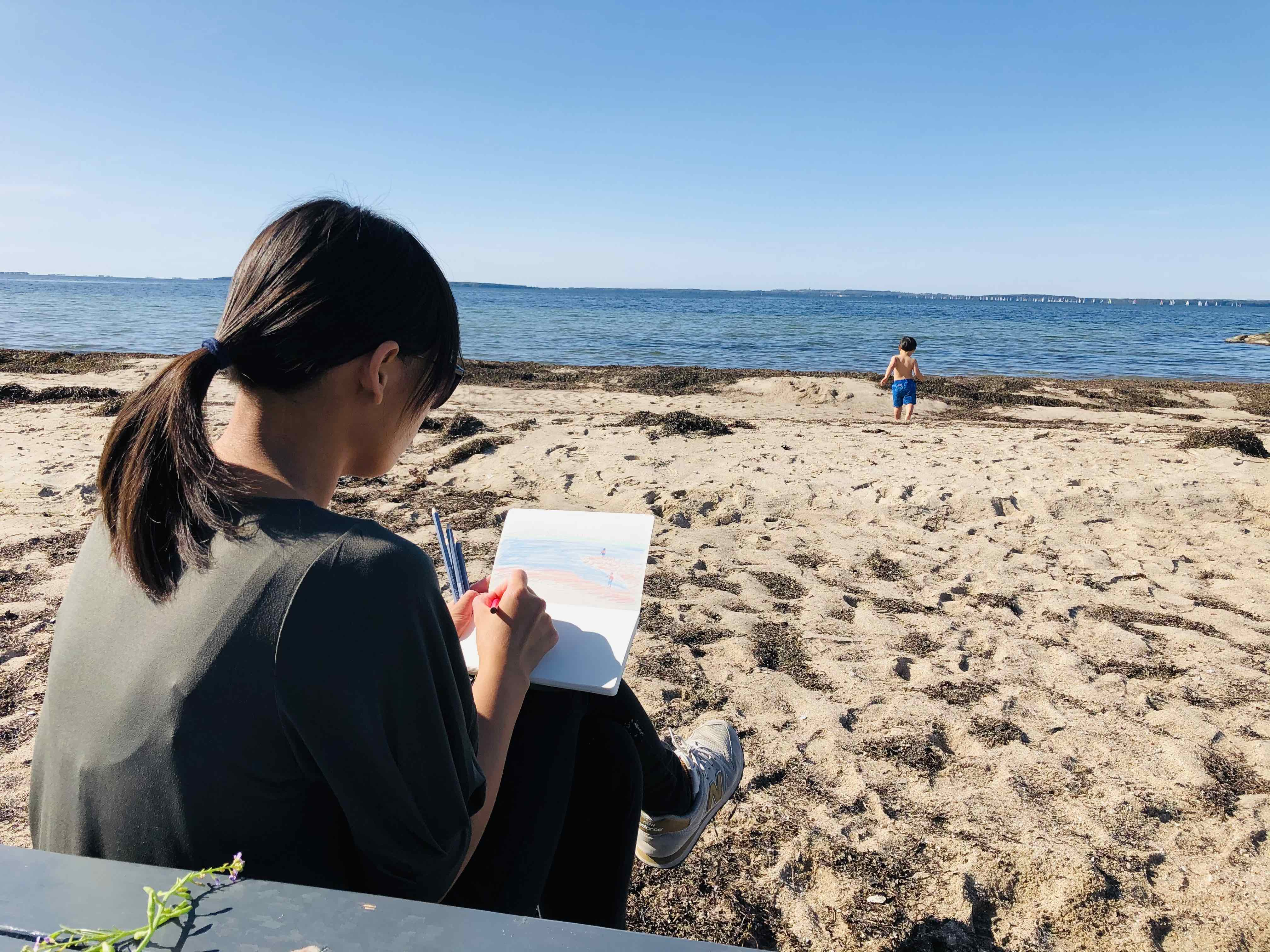 A photo of How Yan Betty Wong sitting at the beach while drawing looking at the ocean ahead