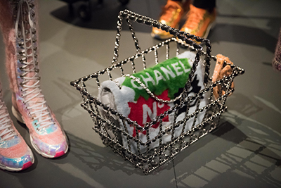 A wire shopping basket holds a rolled Chanel towel