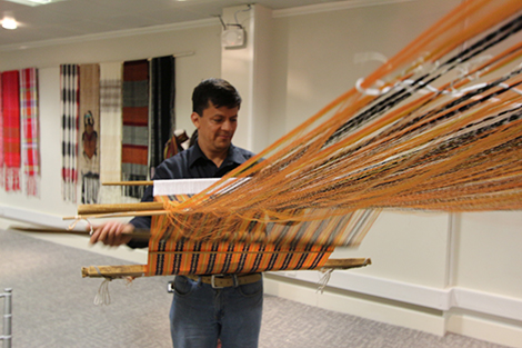 A man using traditional 'backstrap weaving' techniques to create a rebozo at the opening of the exhibition. Photography by Gavin Freeborn.