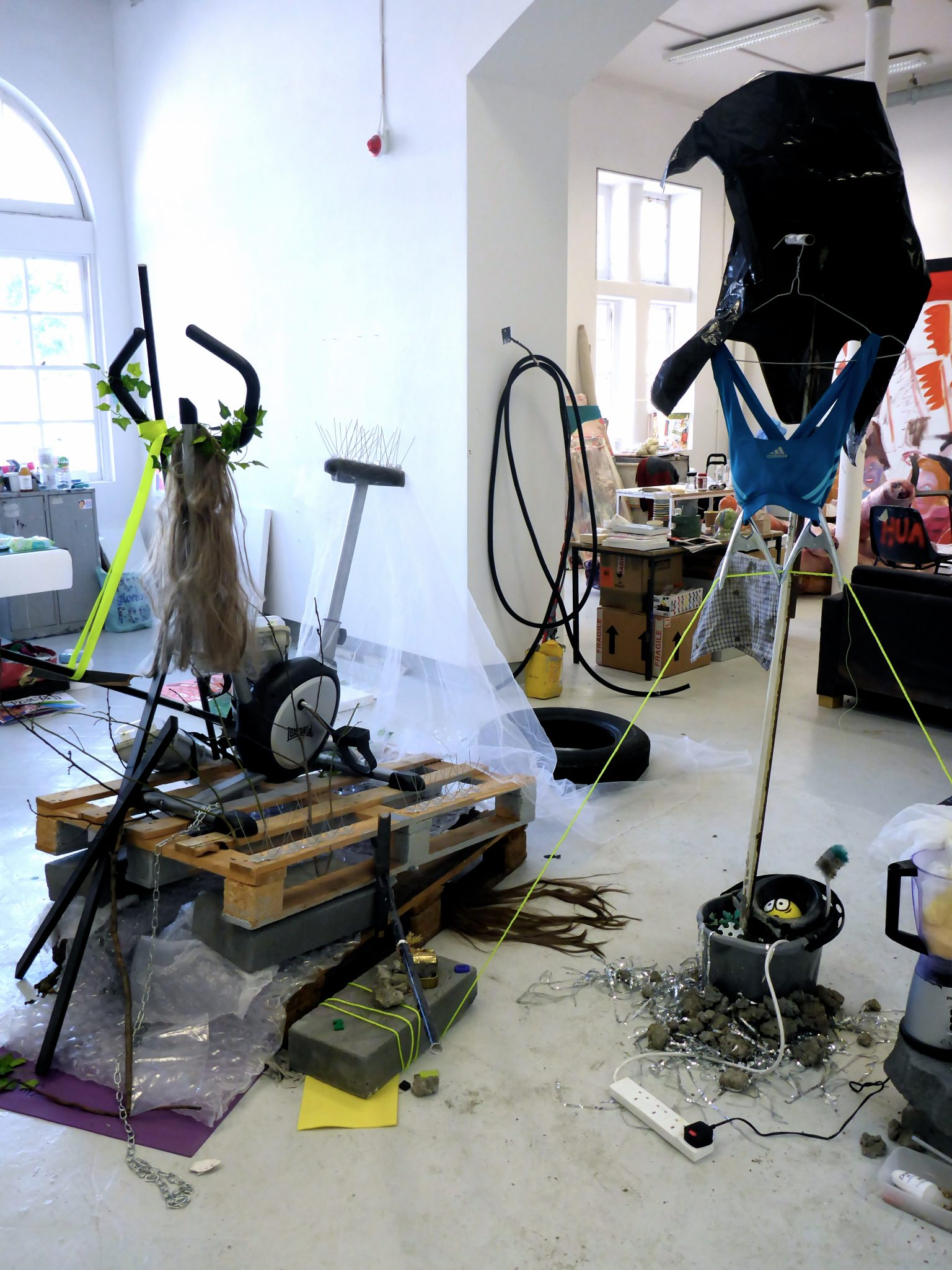 'Woman Laughing Alone Eating Salad The Pyre' and 'Ketosis' (2016) Works in progress. Sculptural assemblage, found objects (Wooden construction palettes, cement, Lonsdale exercise bike, titanium chain, plastic ivy, hair