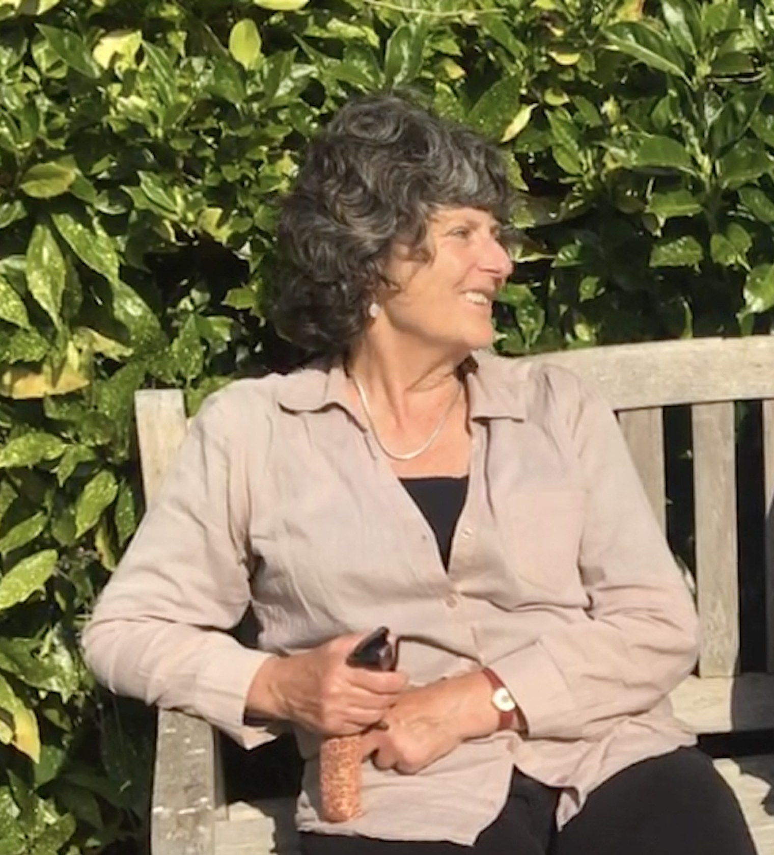 A photo of Sue Bamford sitting on a bench smiling away from the camera