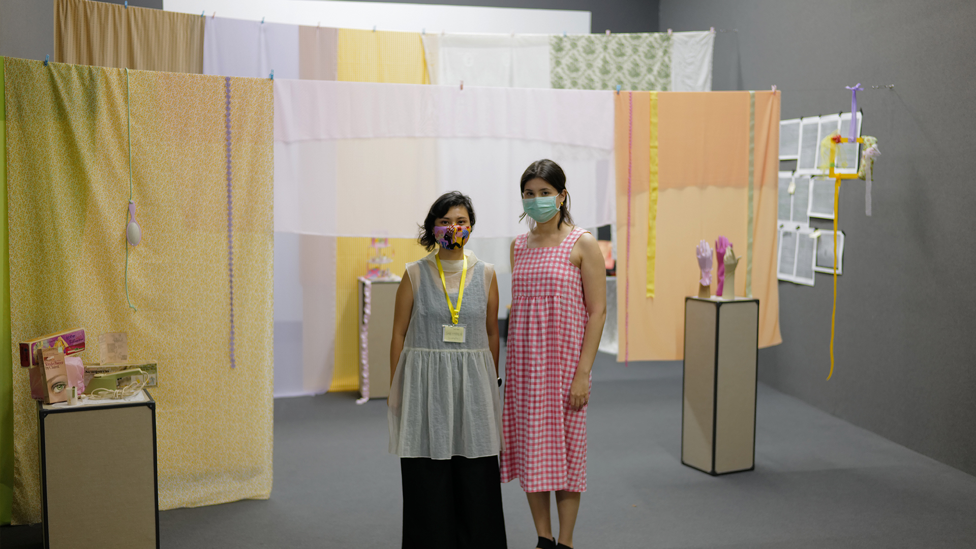 2 women standing in front of a display of textiles