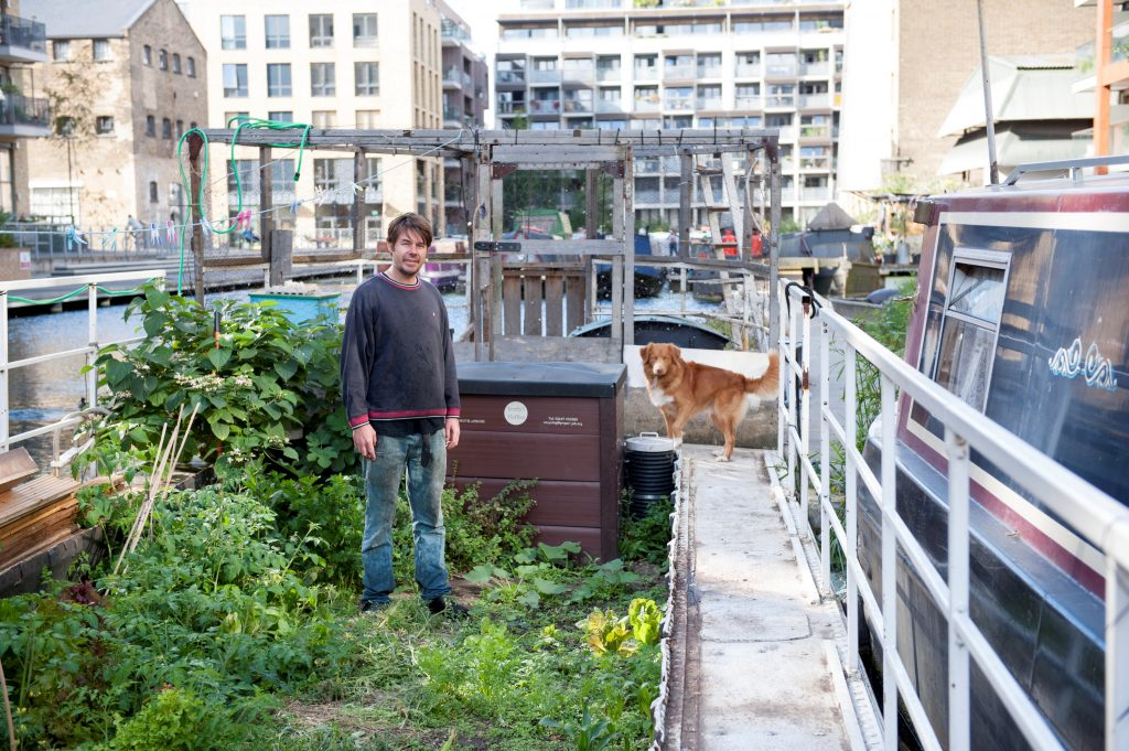 Terry with his dog Manny on their houseboat on the Regents Canal. All 30 residents living on the boats share the gardens. Image by Mary Frances Scott.