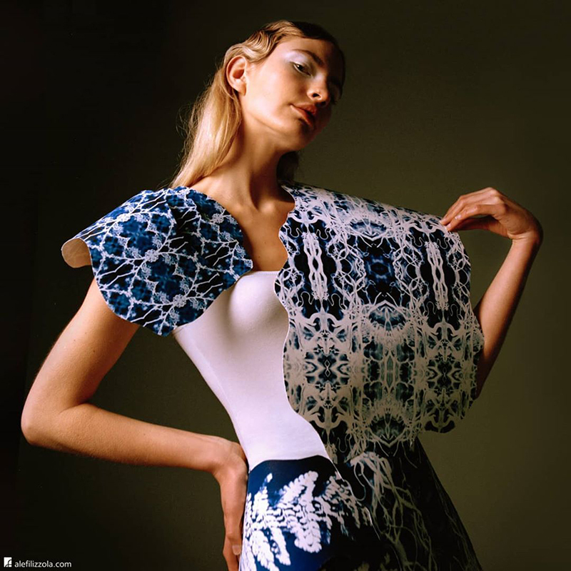 Female model wearing white top and blue and white cape and skirt