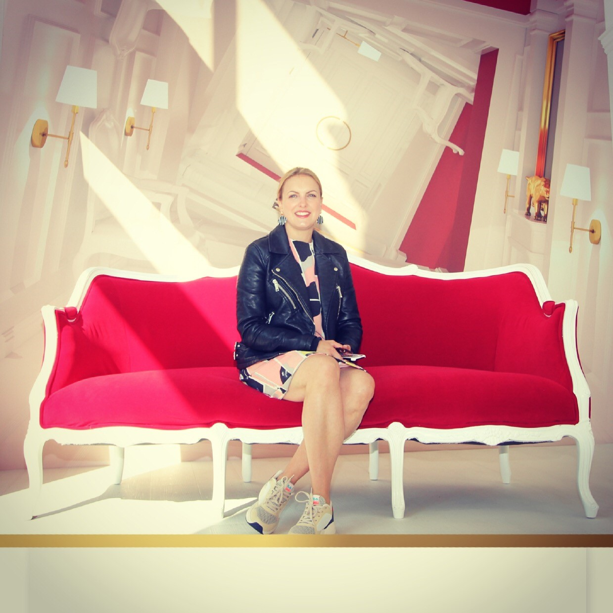 A Photo of Sarah Manning siting on a red seat smiling directly at the camera.