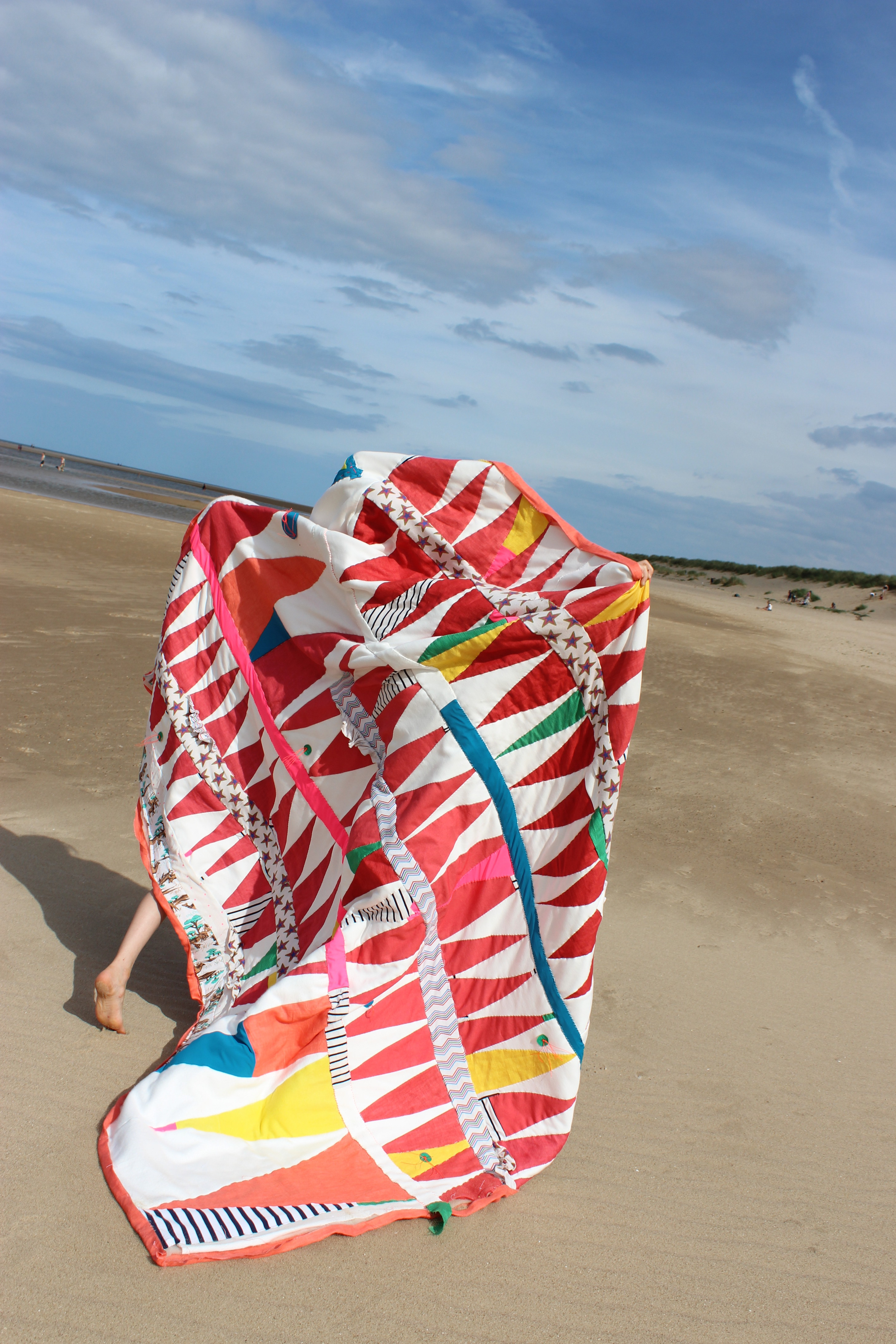 A photo of a quilt being carried overhead on the beach