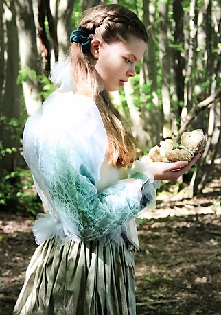 A model stands in a forest looking away from the camera wearing a garment inspired by the pre-Raphaelite art movement