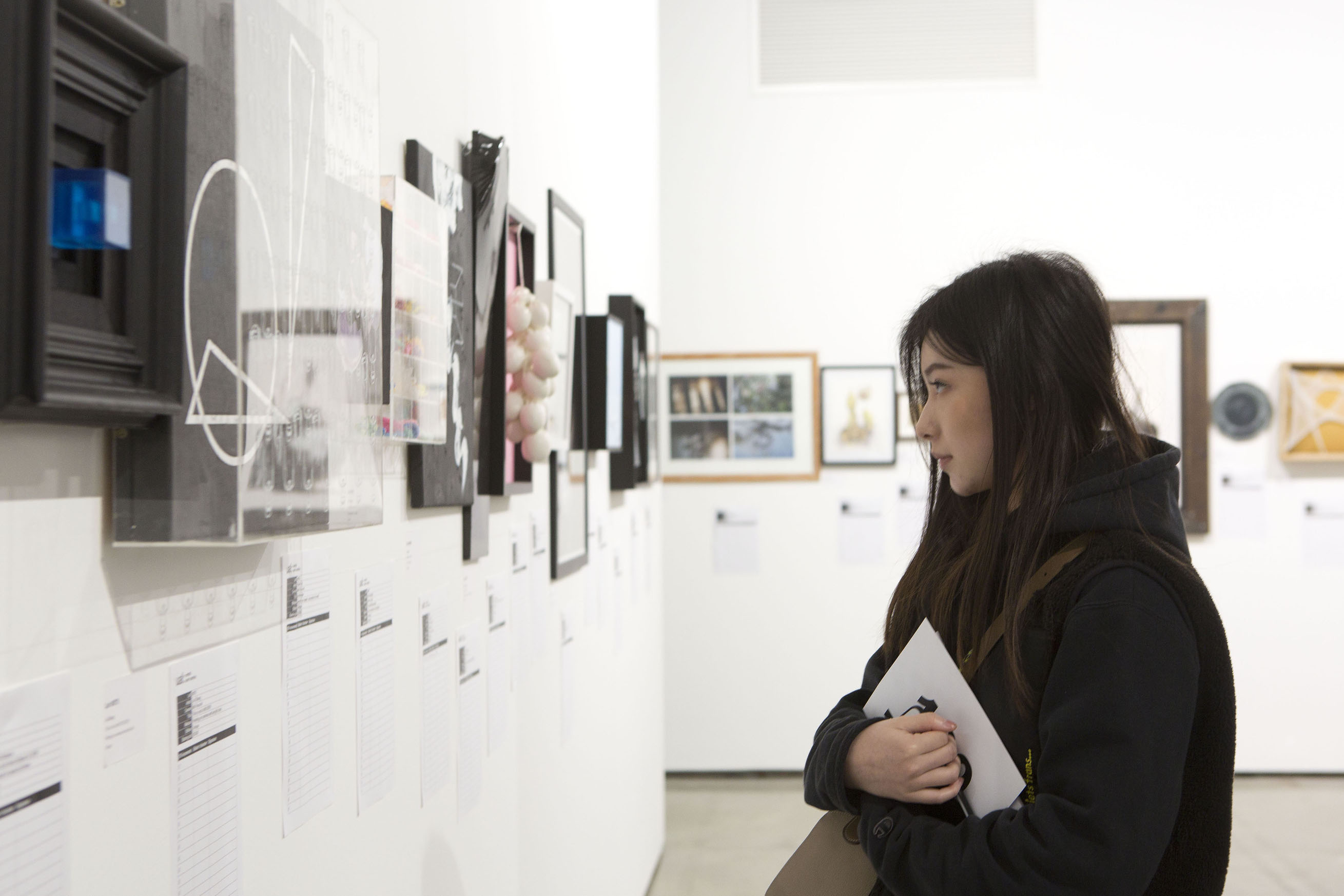 side profile image of a woman looks at artwork on a gallery wall